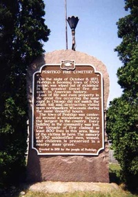 The state historical marker—erected at the Peshtigo Fire Cemetery in 1951—with torch for perpetual flame.